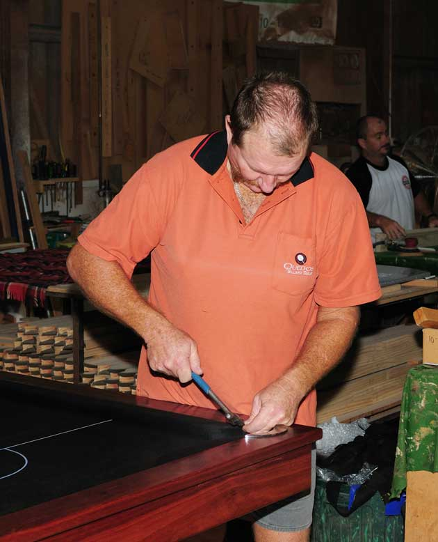 Staff member working on a pool table