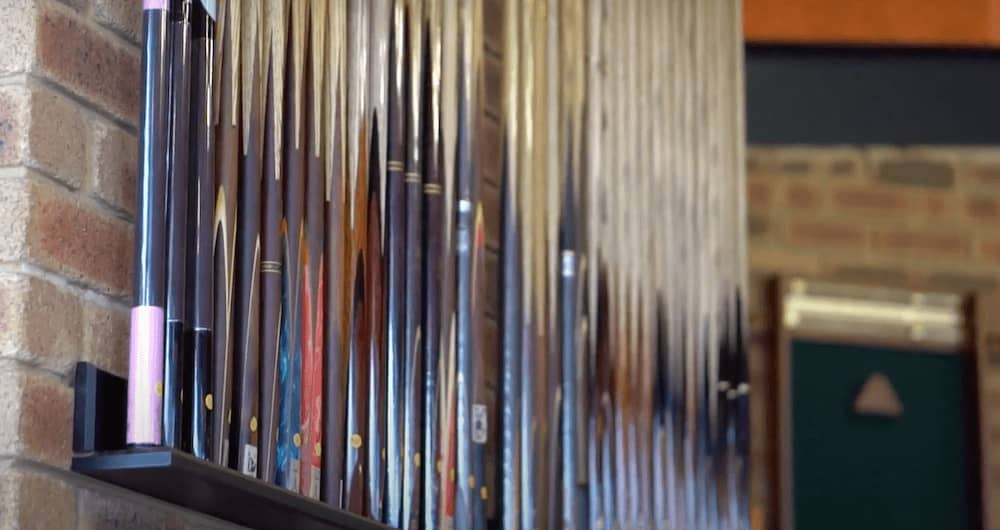 A large commercial style cue rack in the Quedos showroom displaying a huge variety of new pool cues.