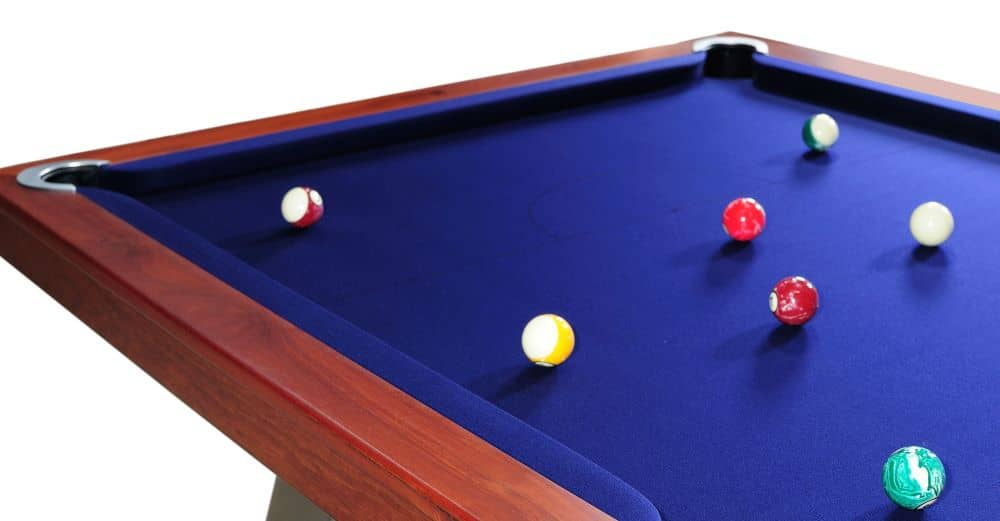 A pool table with quality cushions and rails and blue felt.