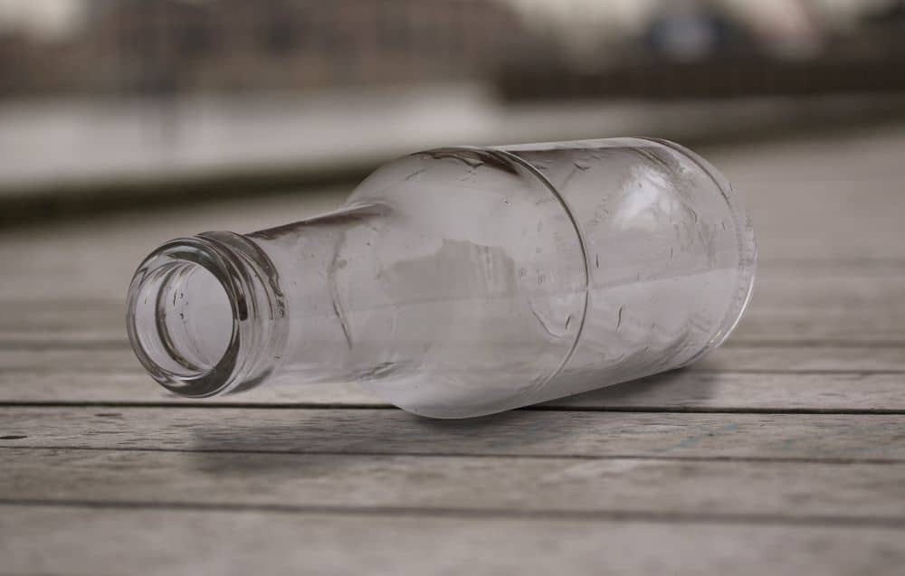 Empty bottle lying on surface of the table.